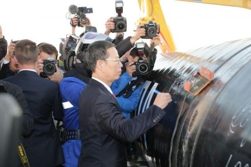 Первый заместитель премьера Государственного совета КНР Ч. Гаоли расписывается на стыке трубы на церемонии соединения первого звена магистрального газопровода «Сила Сибири». 2014 г.